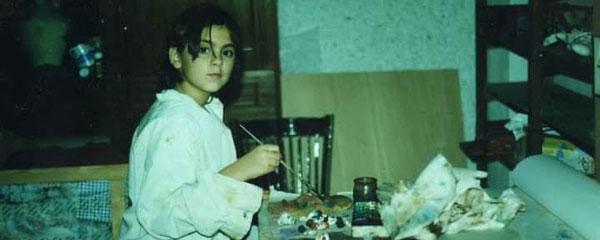 Imagen de Adela, durante su infancia, rodeada de acuarelas y pinturas.